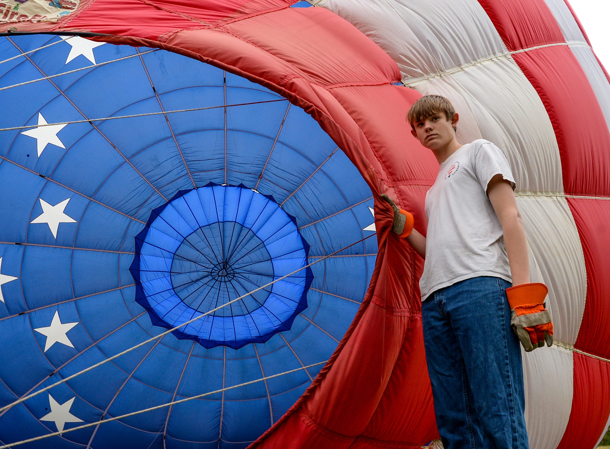 Ryan Sawin of North Carolina helps the Freedom Flyers balloon get inflated before flying over Rocky River Plantation for the Cancer Association of Anderson Hot Air Balloon Affair in Anderson Friday. The event fundraiser helps the non-profit with helping cancer patients with financial needs and support, which the group executive director Angela Stringer said had 5,000 contacts.