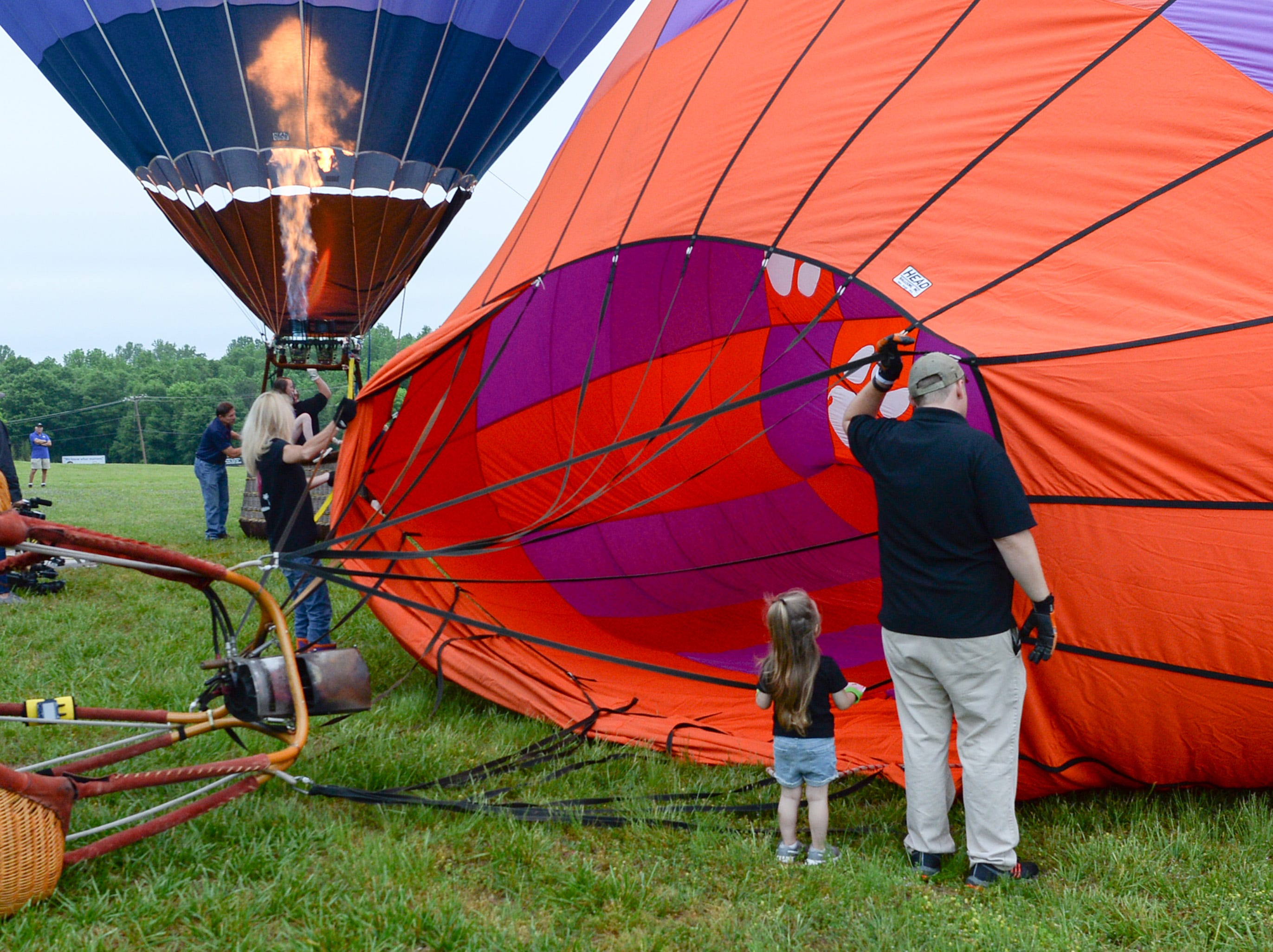 Addy Nelson, 3, left, and her father Braden Nelson of Anderson help inflate the Palmetto Paws hot air balloon before flying over Rocky River Plantation for the Cancer Association of Anderson Hot Air Balloon Affair in Anderson Friday. The event fundraiser helps the non-profit with helping cancer patients with financial needs and support, which the group executive director Angela Stringer said had 5,000 contacts.