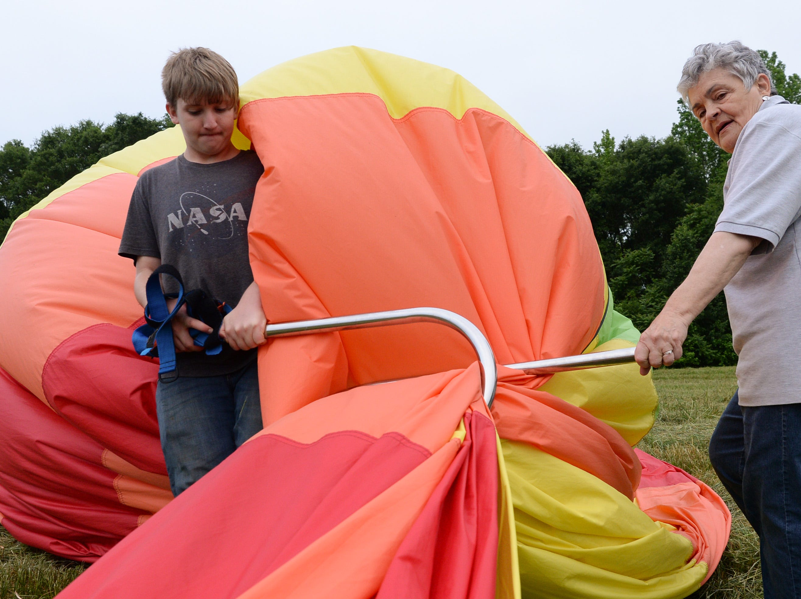 "Sammy Mathis, left, 15, helps Judy Mullinax collect their hot air balloon after flying over Rocky River Plantation for the Cancer Association of Anderson Hot Air Balloon Affair in Anderson Friday. The event fundraiser helps the non-profit with helping cancer patients with financial needs and support, which the group executive director Angela Stringer said had 5,000 contacts. ""This is an opportunity for cancer patients, survivors, and their families and caregivers to come out and have a weekend of just peace, and enjoy the balloons. It's just a way to rise above cancer,"" cancer survivor Stringer said."