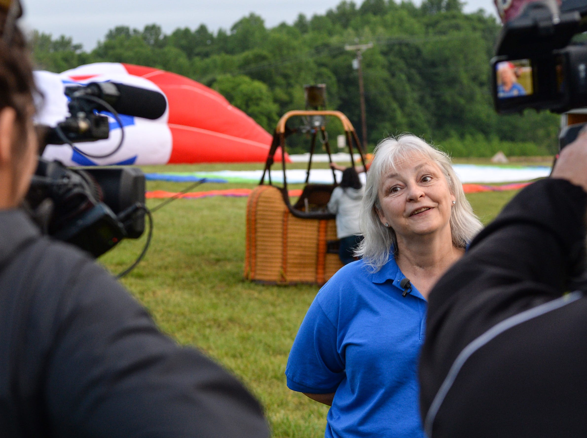 "Angela Stringer, executive director of the Cancer Association of Anderson speaks to media before a morning flight over Rocky River Plantation for the Cancer Association of Anderson Hot Air Balloon Affair in Anderson Friday. The event fundraiser helps the non-profit with helping cancer patients with financial needs and support, which the group executive director Angela Stringer said had 5,000 contacts. ""This is an opportunity for cancer patients, survivors, and their families and caregivers to come out and have a weekend of just peace, and enjoy the balloons. It's just a way to rise above cancer,"" cancer survivor Stringer said."