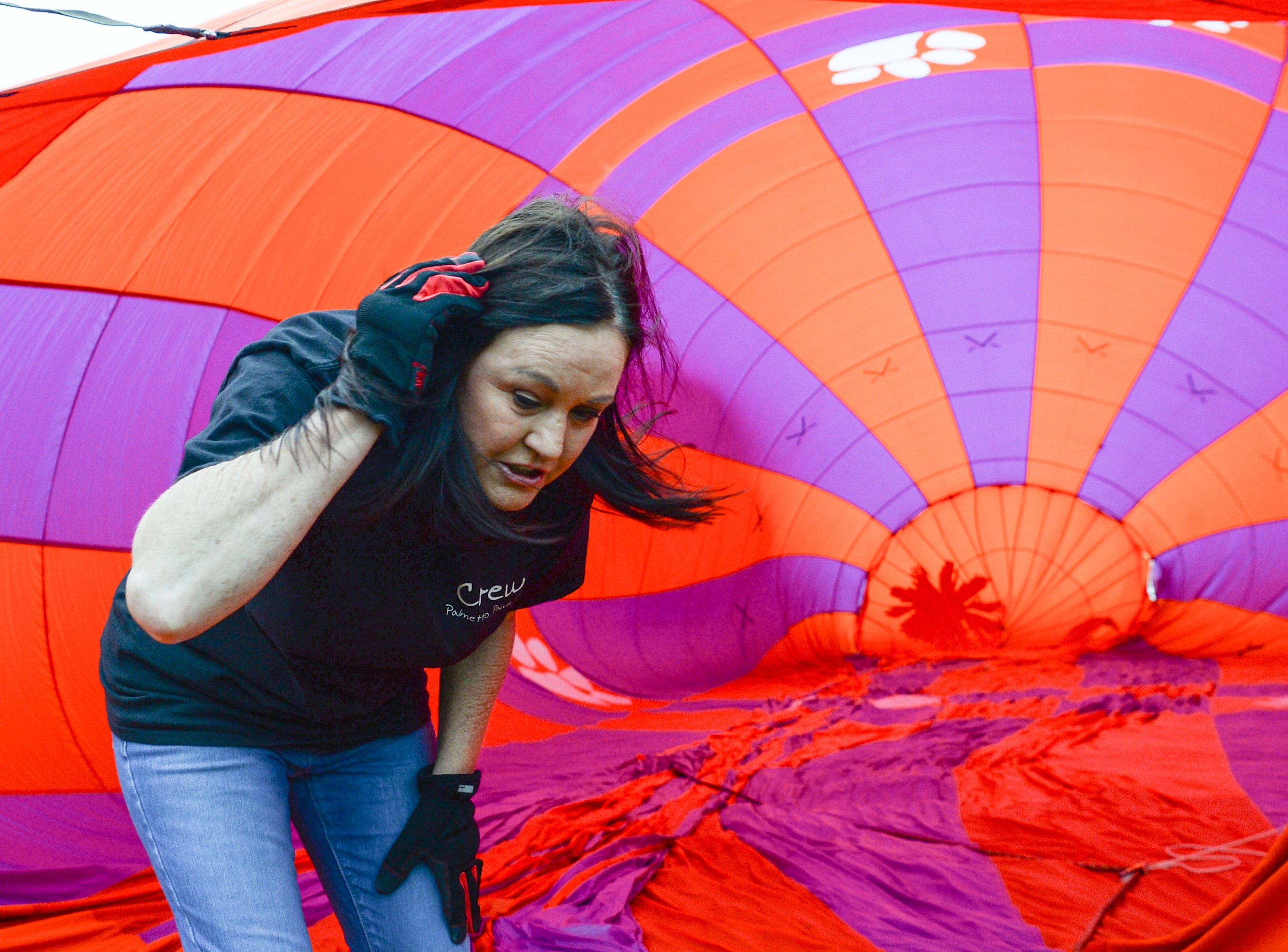 "Pilot Donna Hendershot of Anderson helps inflate the Palmetto Paw balloon during a flight over Rocky River Plantation for the Cancer Association of Anderson Hot Air Balloon Affair in Anderson Friday. The event fundraiser helps the non-profit with helping cancer patients with financial needs and support, which the group executive director Angela Stringer said had 5,000 contacts. ""This is an opportunity for cancer patients, survivors, and their families and caregivers to come out and have a weekend of just peace, and enjoy the balloons. It's just a way to rise above cancer,"" cancer survivor Stringer said."