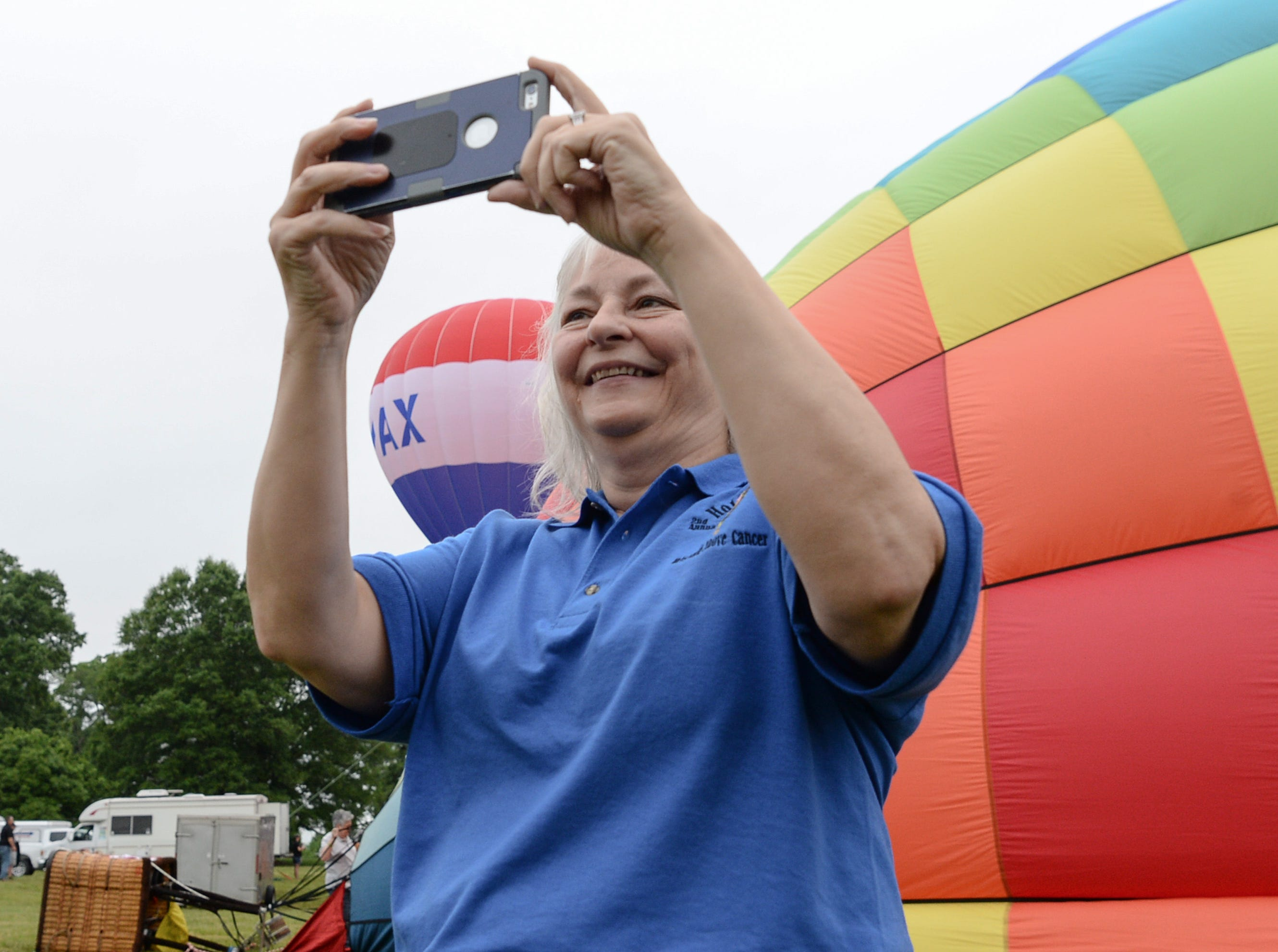 "Angela Stringer, executive director of the Cancer Association of Anderson gets photos during a morning flight over Rocky River Plantation for the Cancer Association of Anderson Hot Air Balloon Affair in Anderson Friday. The event fundraiser helps the non-profit with helping cancer patients with financial needs and support, which the group executive director Angela Stringer said had 5,000 contacts. ""This is an opportunity for cancer patients, survivors, and their families and caregivers to come out and have a weekend of just peace, and enjoy the balloons. It's just a way to rise above cancer,"" cancer survivor Stringer said."