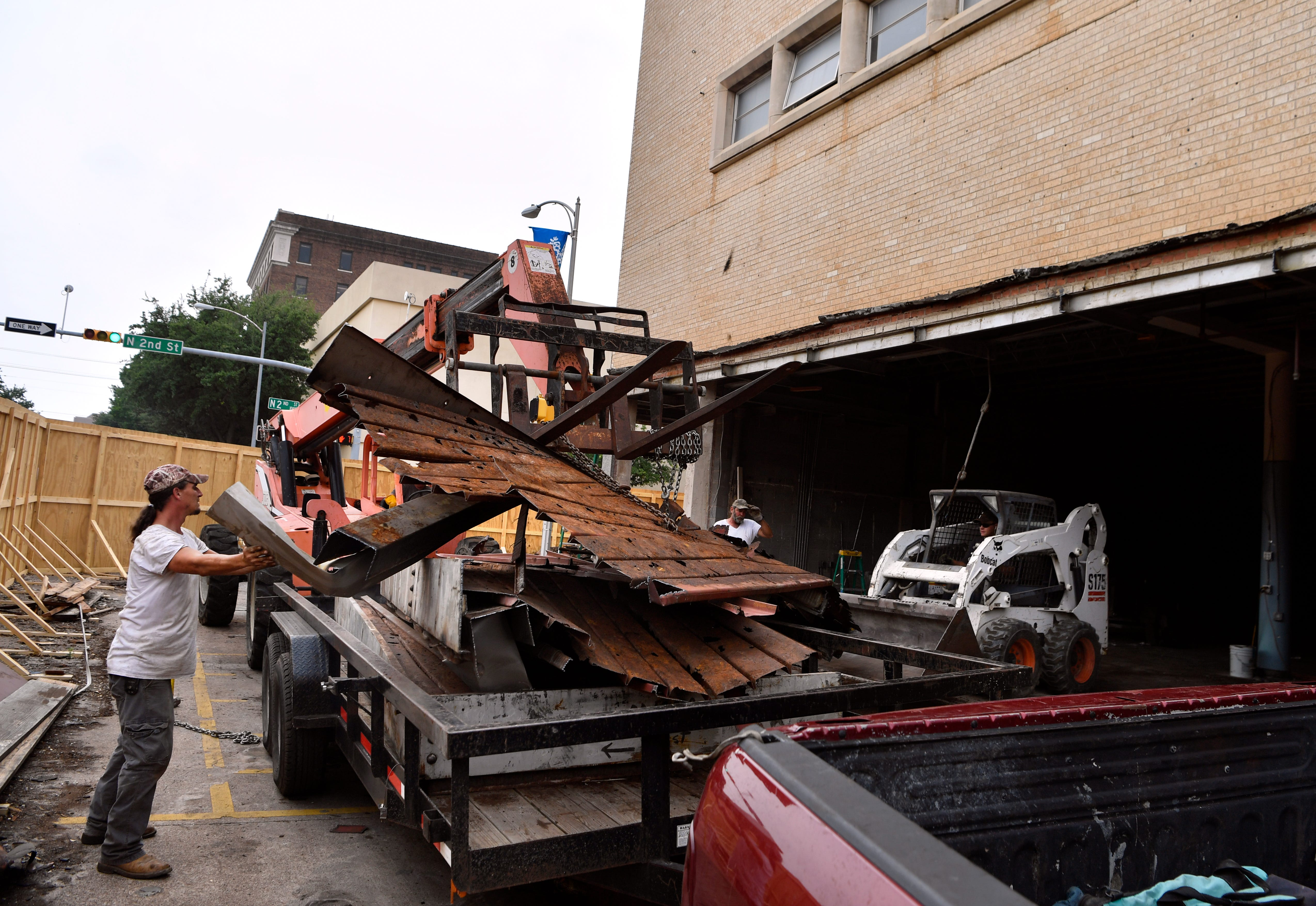 Jonathan Peters steadies the remains of the steel awning as Adair Hanley lowers it onto a trailer April 30 at 202 Pine St. The renovated building will be known as the Motis Building and will be home to several new downtown businesses.