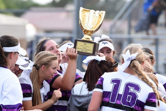 The Wylie softball team celebrates with the Region I-5A area championship trophy after sweeping El Paso Eastwood 14-5 and 7-5 in Pecos on Thursday, May 2, 2019.
