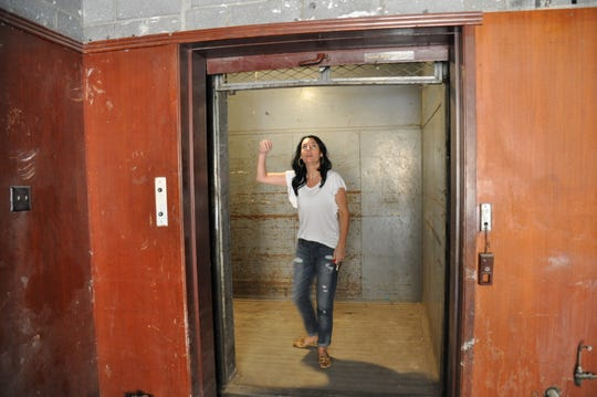 Tiffany Gutierrez moves the overhead door to the freight elevator in the Motis Building on April 5. Renovations of the building will include replacing the operational elevator to meet new building codes.
