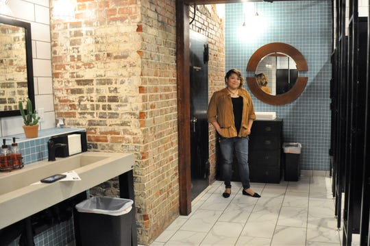 Crystal Holladay, vice president of operations at Wolfe Development Inc., stands next to the original walk-in safe that is now part of the new restrooms at 201 Mesquite Event Center. The rental facility in a former downtown grocer warehouse built in 1903 first opened in 2017 with pop-up Eller Hall dances.