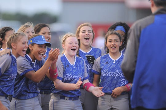 The Stamford softball team cheers as its area-playoff trophy is presented after an 8-1 win over Miles on Thursday, May 2, 2019, in Hermleigh.