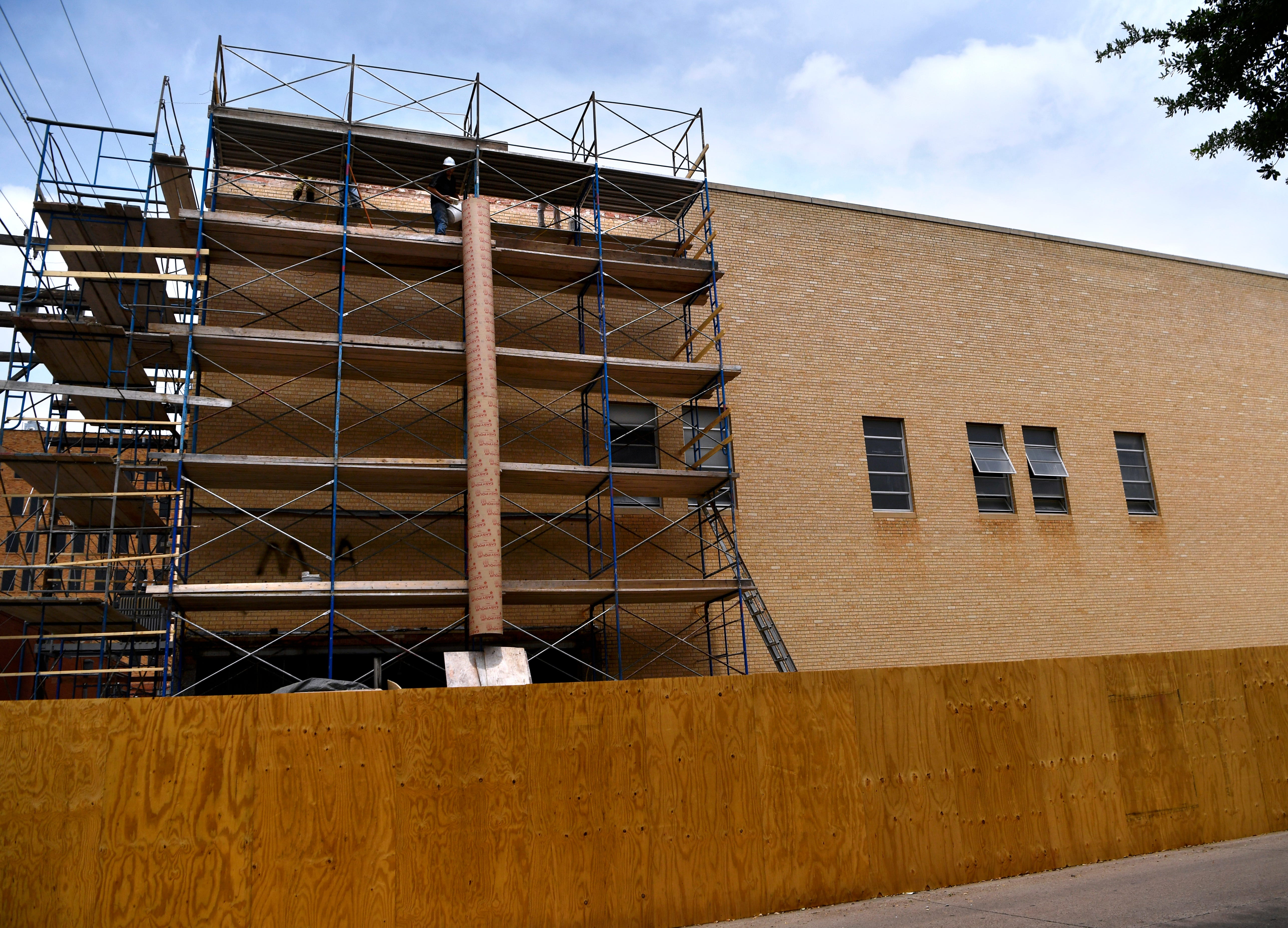 Workers on April 30 remove the yellow brick covering 202 Pine St. The renovated building will be known as the Motis Building and will be home to several new downtown businesses.