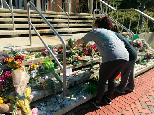 Mourners pause to look at a variety of memorials left at Kennedy Hall at UNC Charlotte on Thursday, May 2, 2019. A gunman opened fire at Kennedy on April 30, killing two and wounding four.