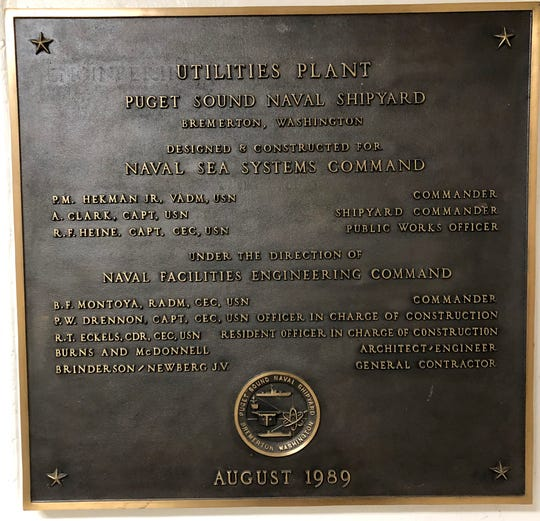Inside the steam plant, a dedication plaque marks the month — August 1989 — when the plant, initially fueled by coal, started up.