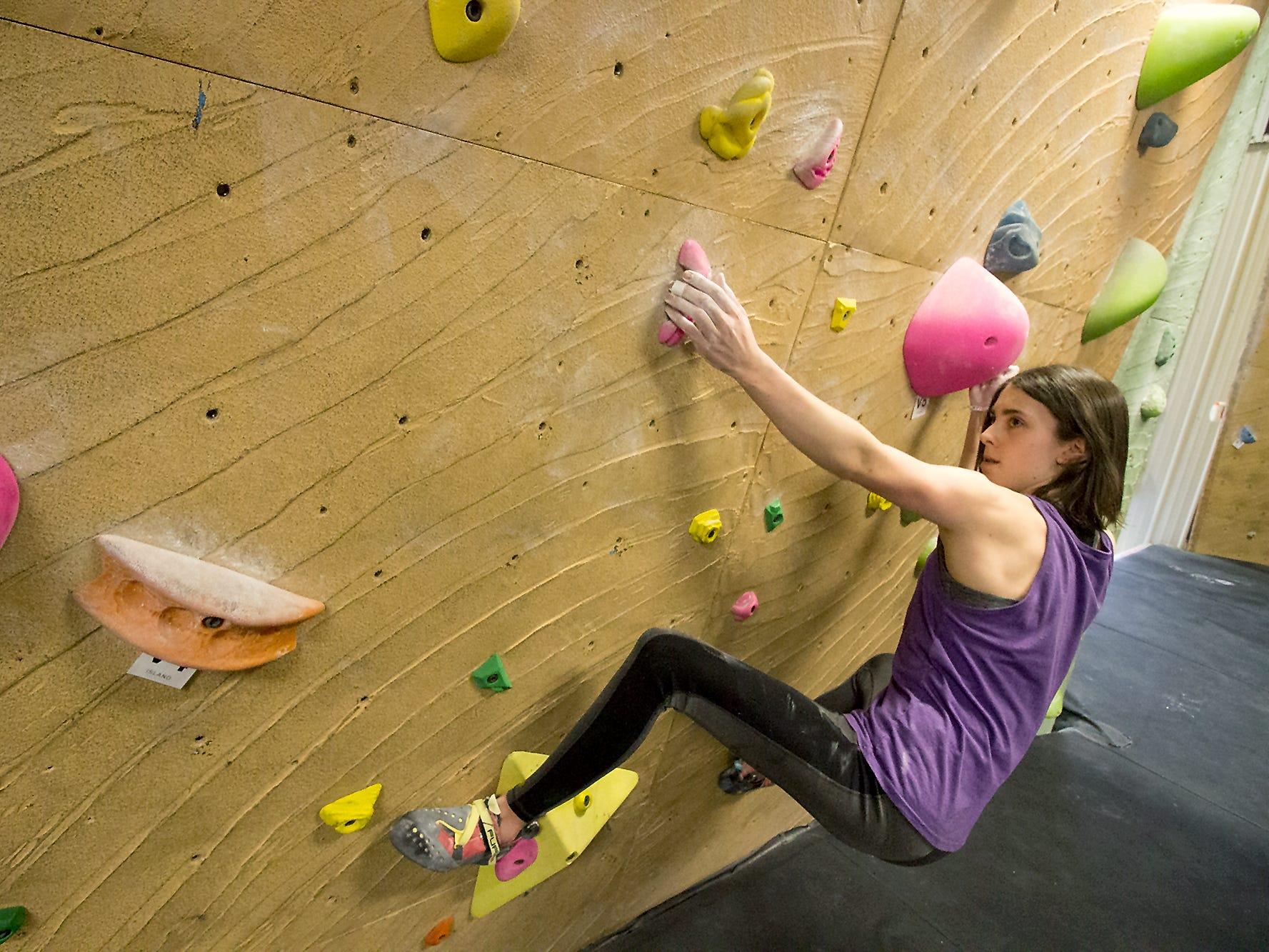 Ella McRitchie eyes a climbing route at the Island Rock Gym on Bainbridge Island.
