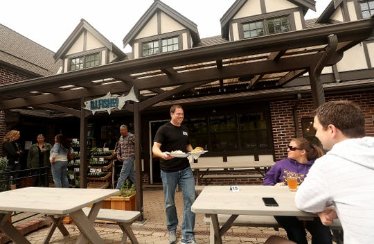 Co-owner Jess Goldwater carries plates of fish tacos and a fish sandwich out to the diners on the patio of The Bainbridge Island Fish Company in Lynwood Center on Bainbridge Island.