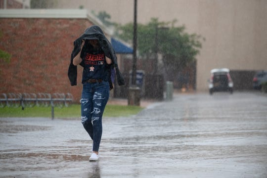 A women covers her head as she walks through the University of Texas-Corpus Christi during a rain storm in Corpus Christi on Friday, May 3, 2019. A system of severe thunderstorms were forecast to move over South Texas bringing high winds and potential hail.