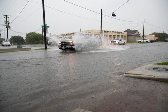 A car drives thought standing water on Santa Fe Street in Corpus Christi as storms dump rain and bring high winds to the area on Friday, May 3, 2019.