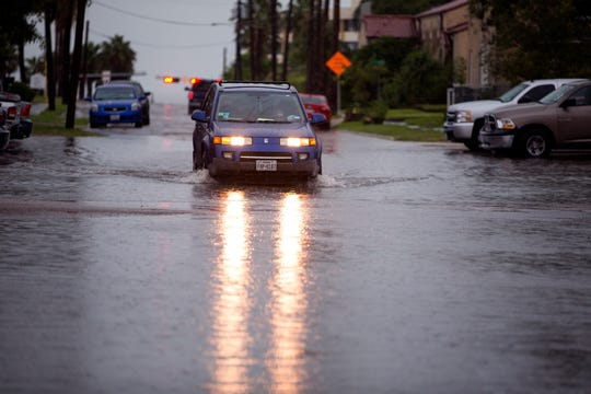 A driver passes through a flooded road at Buford and Third streets on Friday, May 3, 2019. A system of severe thunderstorms were forecast to move over South Texas bringing high winds and potential hail.