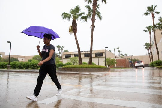 A women walks across the street with an umbrella during rainfall at the University of Texas-Corpus Christi on Friday, May 3, 2019. A system of severe thunderstorms were forecast to move over South Texas bringing high winds and potential hail.