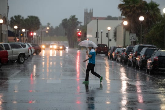 A man walks across the street with an umbrella during rainfall in downtown Corpus Christi on Friday, May 3, 2019. A system of severe thunderstorms were forecast to move over South Texas bringing high winds and potential hail.