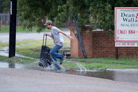 A man jumps over a puddle on Third Street on Friday, May 3, 2019. A system of severe thunderstorms were forecast to move over South Texas bringing high winds and potential hail.