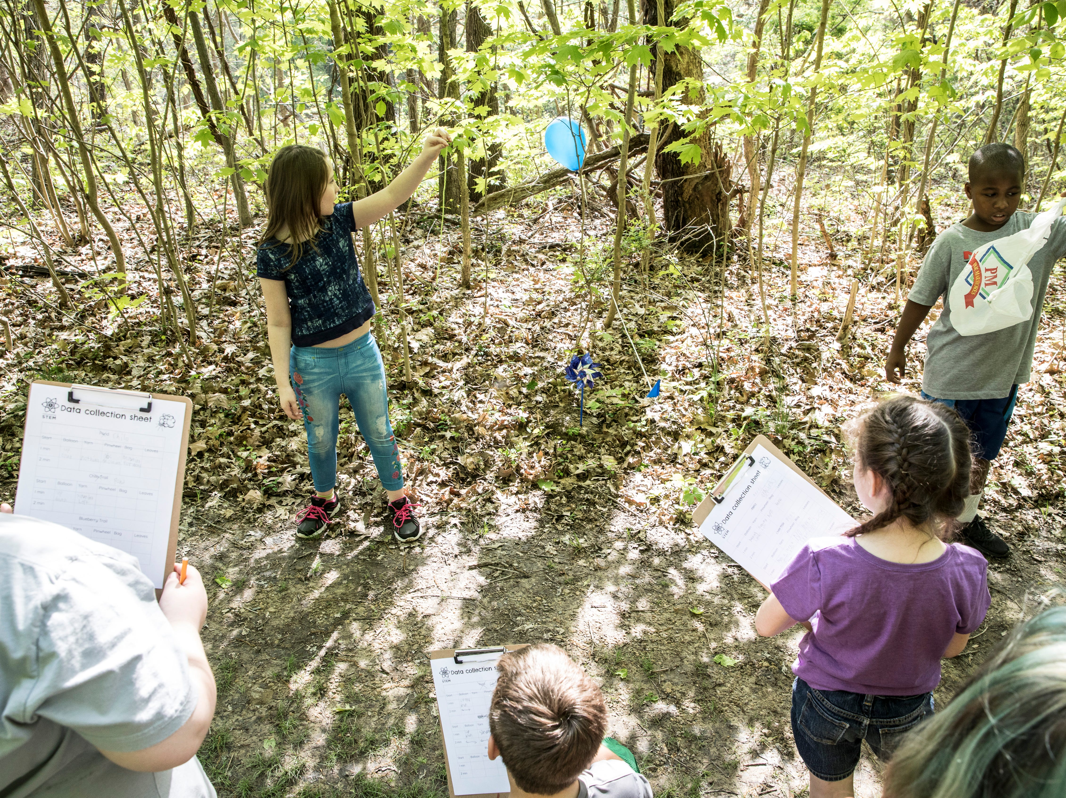 Noelle Eblin, left, and Armani Netter, right, hold up common household objects to see how they will react to the wind while other students write down what they see during a STEM outing at Buzzards Roost Nature Preserve on Wednesday, May 1, 2019.