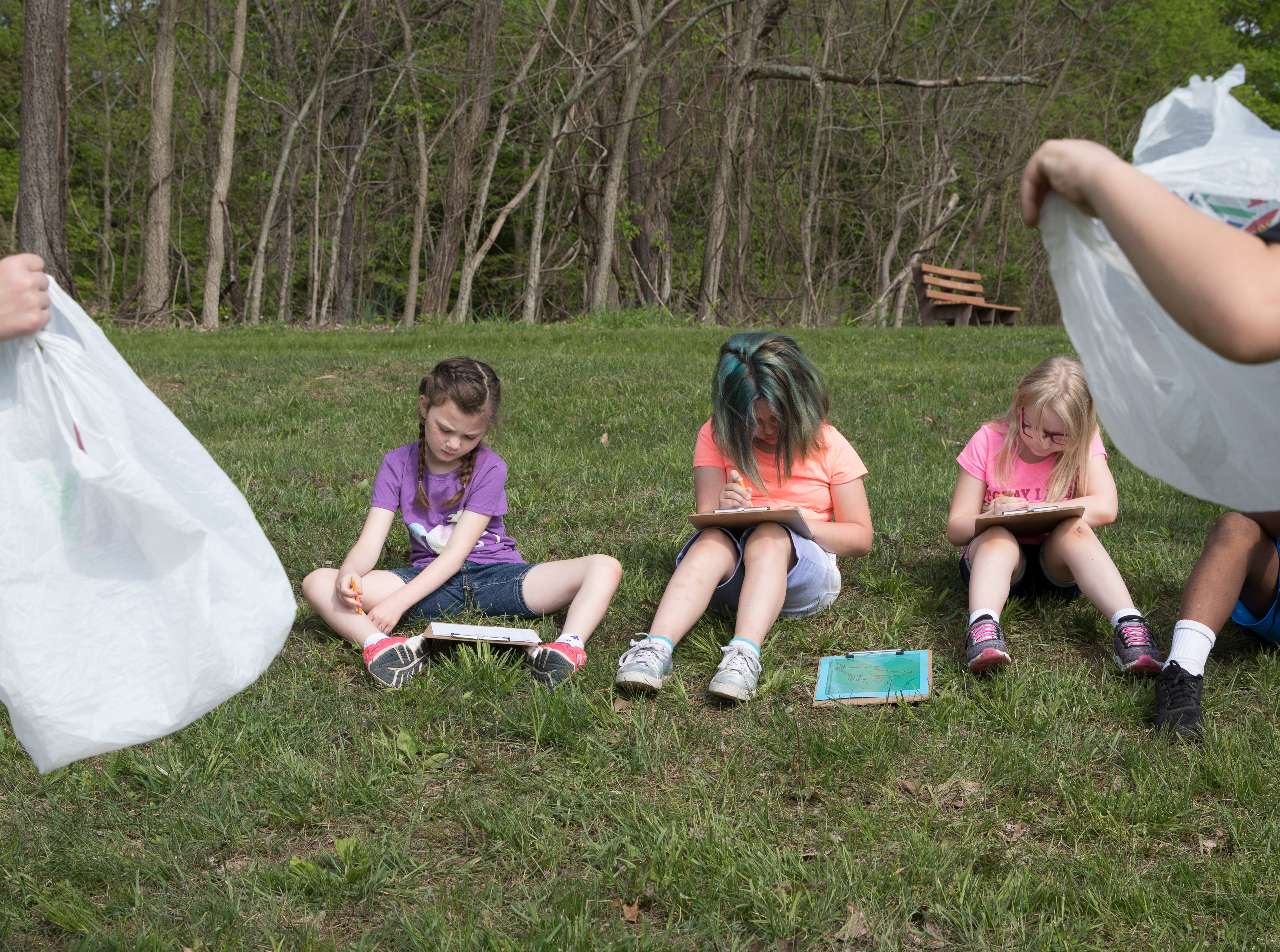 (L-R) Chillicothe Primary School students Angel McDaniel, Echo Fletcher, and Alexis Gibson write down how simple grocery bags react to the changing wind and the strength as to which it blows as part of hand on learning experience crucial to the STEM learning program at Buzzards Roost Nature Preserve on Wednesday, May 1, 2019.