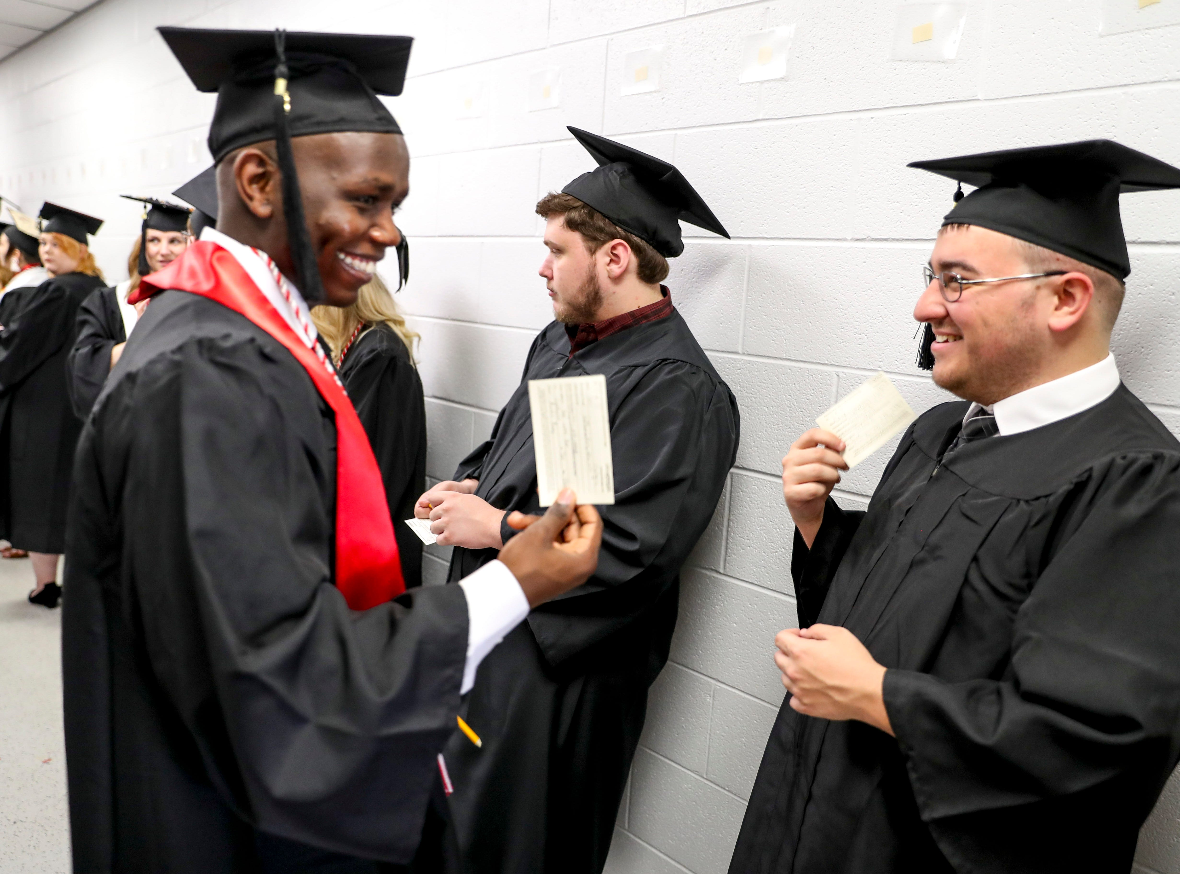 Students joke and wave name cards given to them like small fans in the heat at the Austin Peay spring commencement ceremony 2019 for College of Business and College of STEM at Winfield Dunn Center in Clarksville, Tenn., on Friday, May 3, 2019.