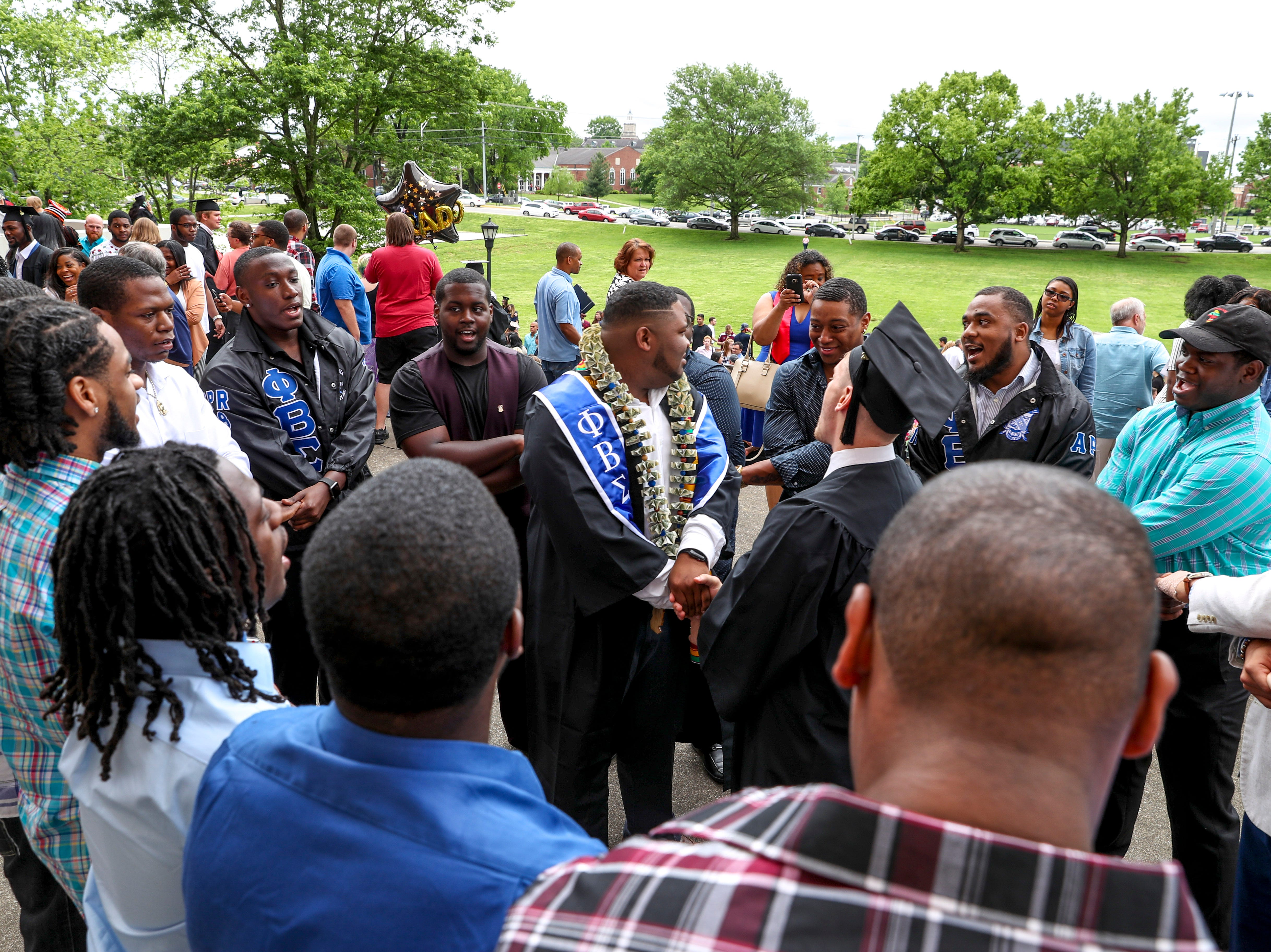 A fraternity sings together around other students at the Austin Peay spring commencement ceremony 2019 for College of Business and College of STEM at Winfield Dunn Center in Clarksville, Tenn., on Friday, May 3, 2019.