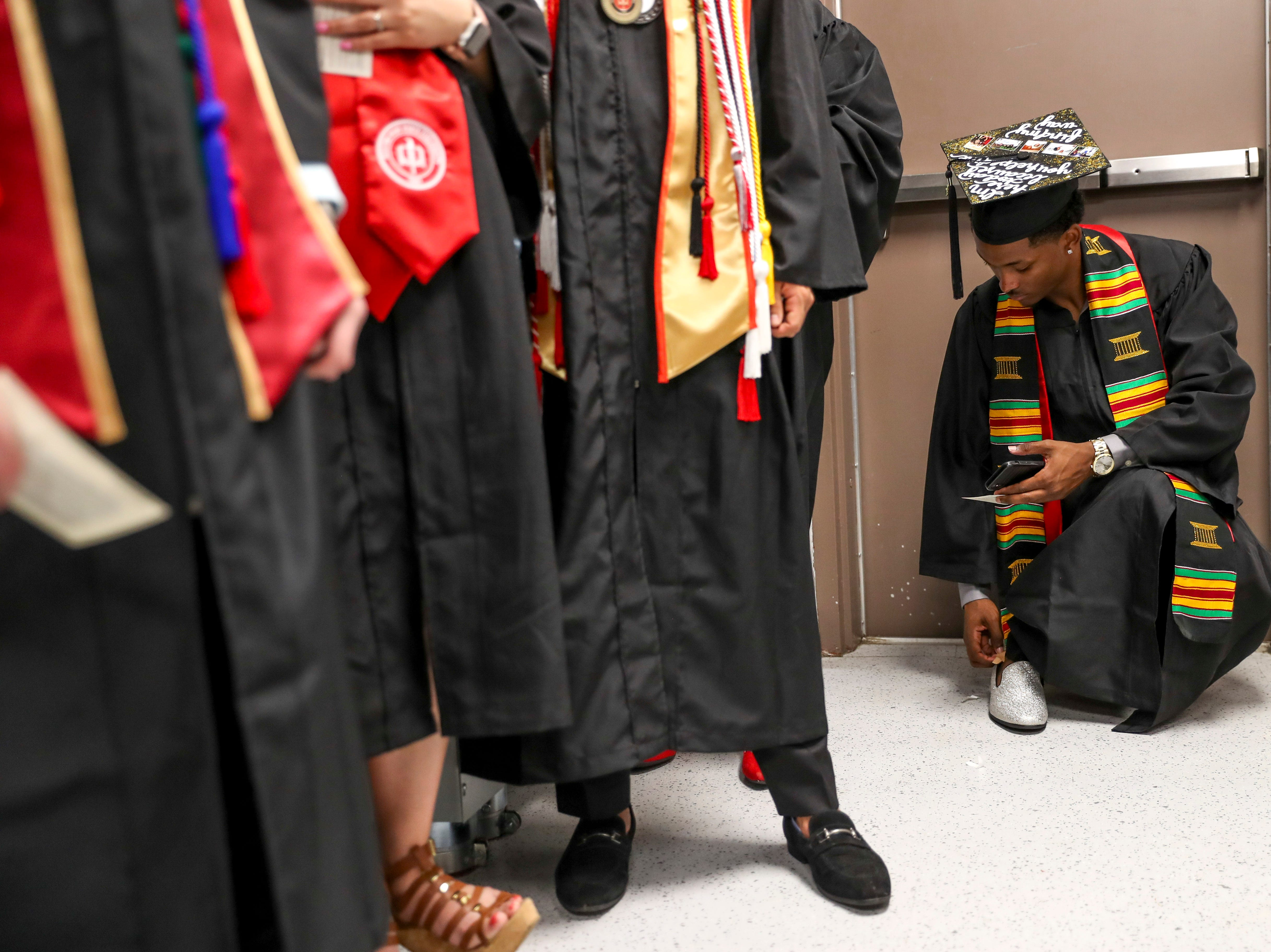 A student checks their socks in the back of the line at the Austin Peay spring commencement ceremony 2019 for College of Business and College of STEM at Winfield Dunn Center in Clarksville, Tenn., on Friday, May 3, 2019.