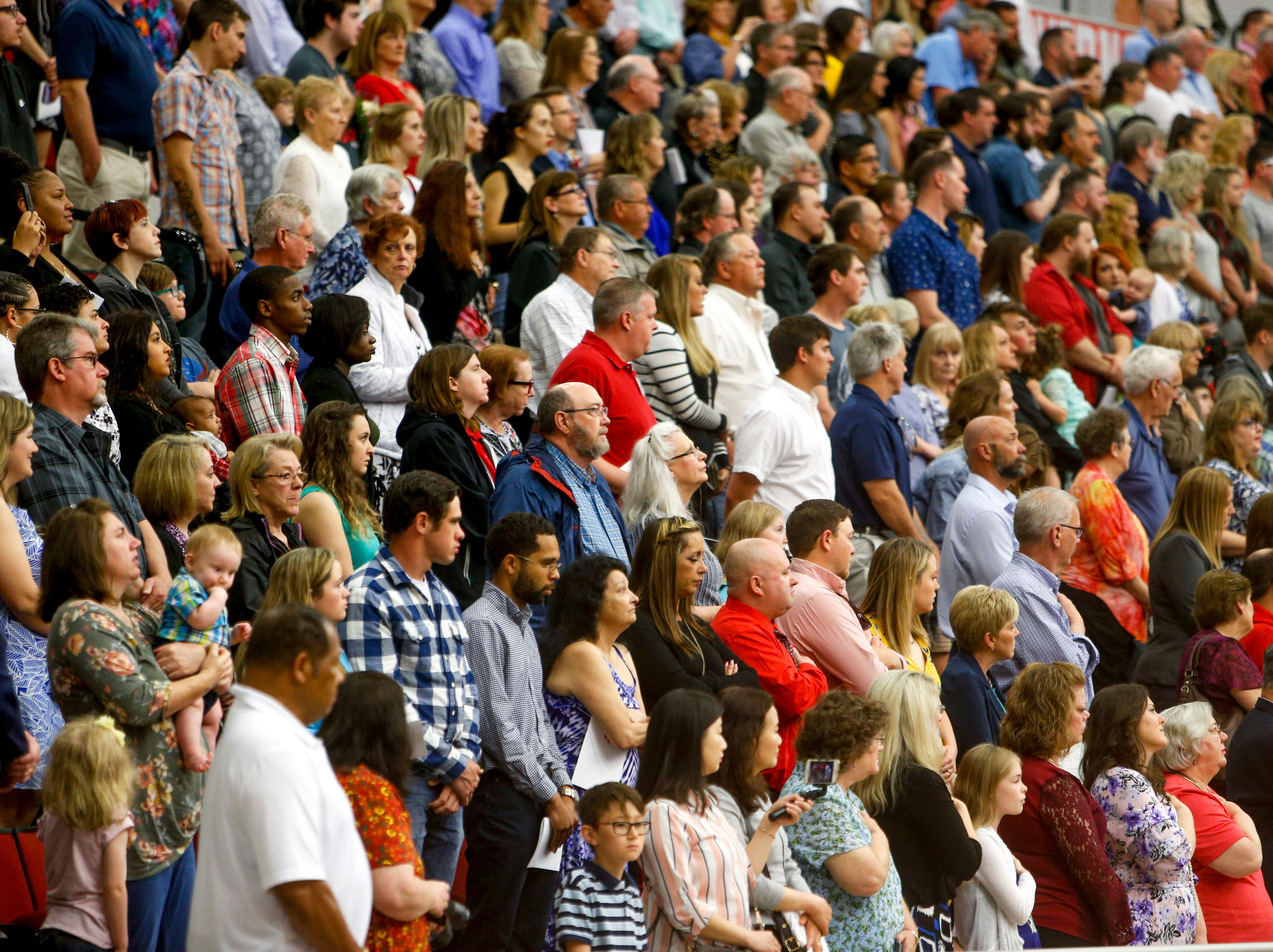 Family and friends stand for the national anthem at the Austin Peay spring commencement ceremony 2019 for College of Business and College of STEM at Winfield Dunn Center in Clarksville, Tenn., on Friday, May 3, 2019.
