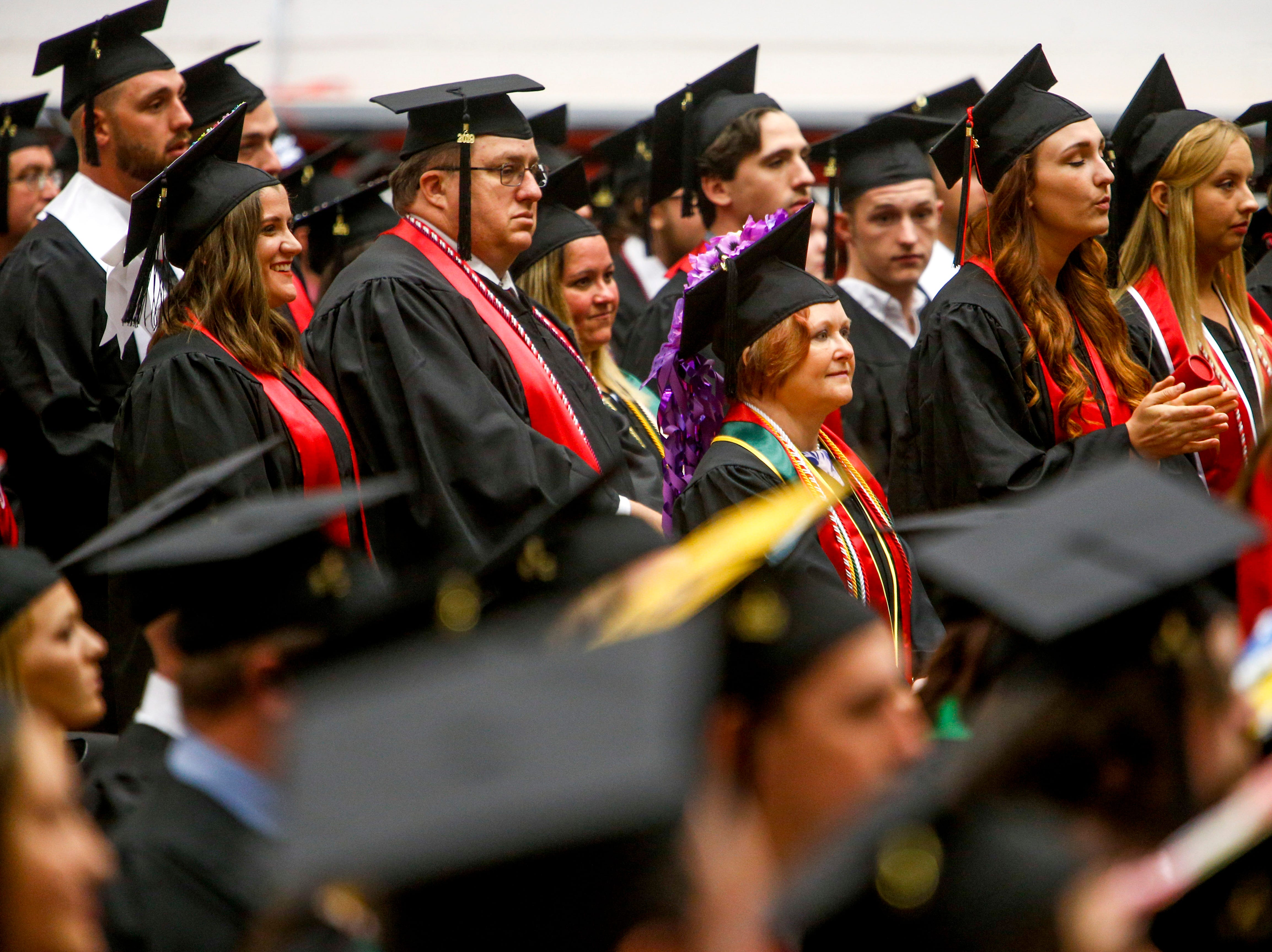 Students stand before walking and receiving their diplomas at the Austin Peay spring commencement ceremony 2019 for College of Business and College of STEM at Winfield Dunn Center in Clarksville, Tenn., on Friday, May 3, 2019.