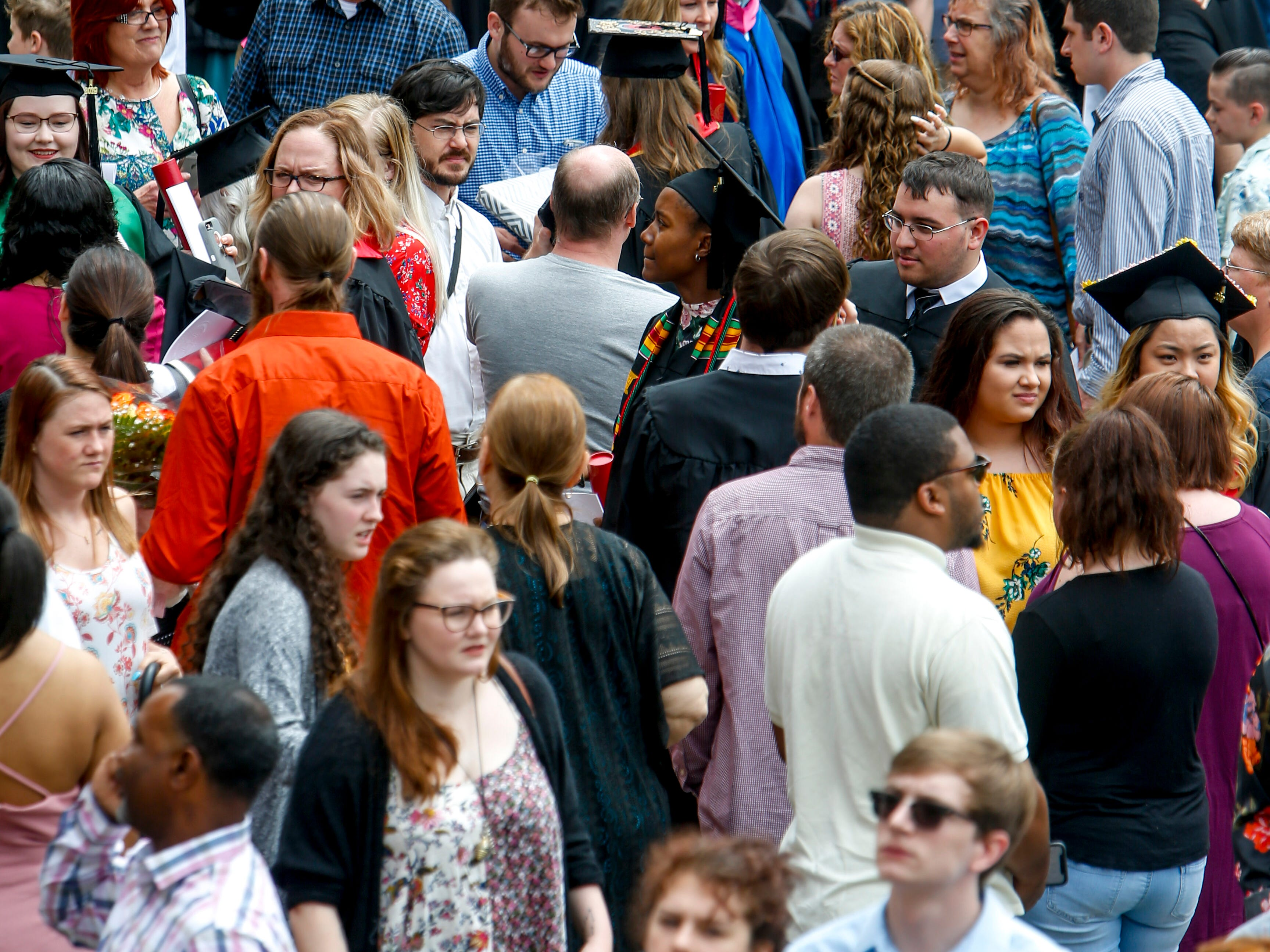 Family and friends mingle with graduates on the outside lawn at the Austin Peay spring commencement ceremony 2019 for College of Business and College of STEM at Winfield Dunn Center in Clarksville, Tenn., on Friday, May 3, 2019.