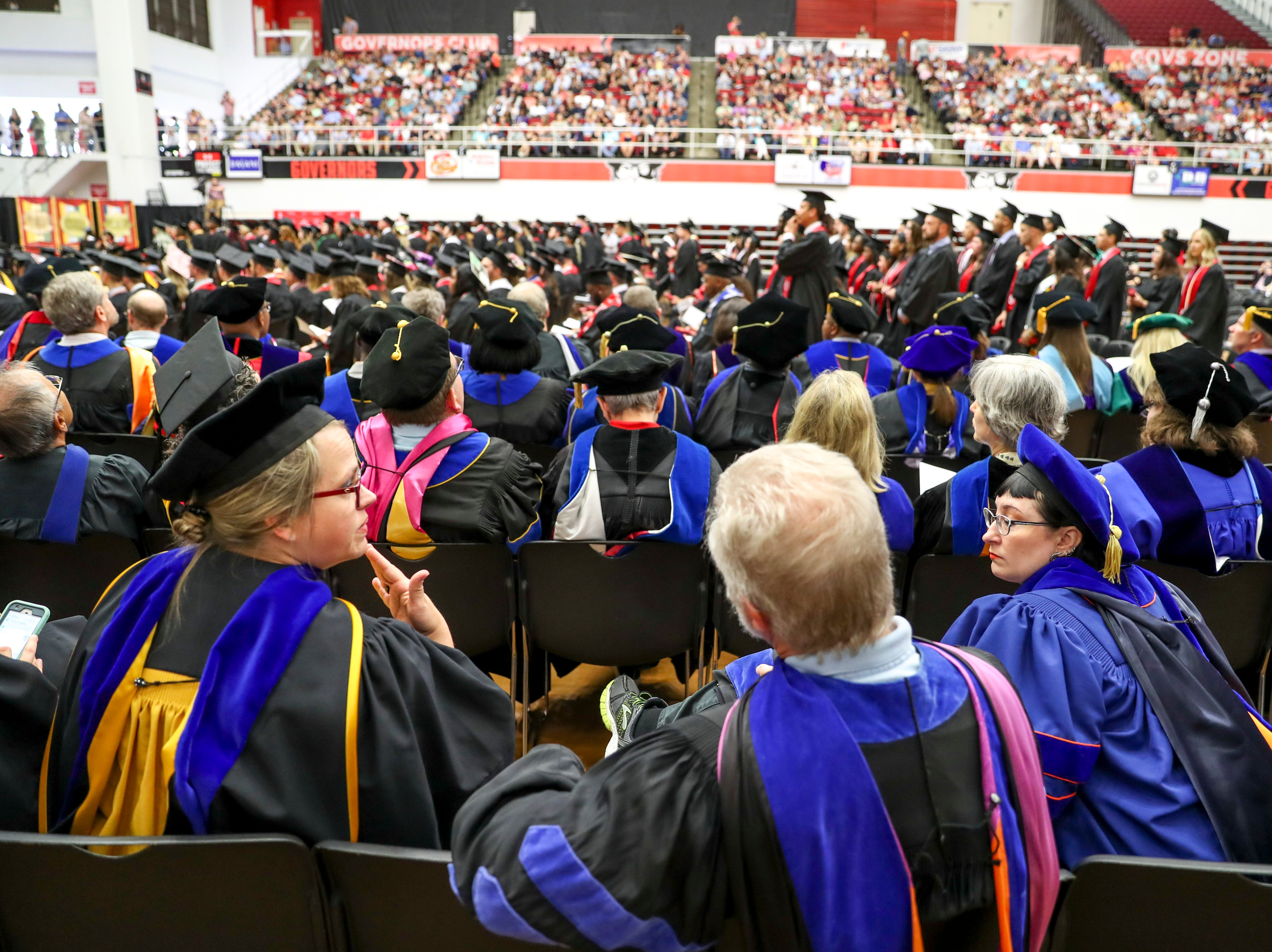 Faculty chat with one another while students are presented diplomas at the Austin Peay spring commencement ceremony 2019 for College of Business and College of STEM at Winfield Dunn Center in Clarksville, Tenn., on Friday, May 3, 2019.