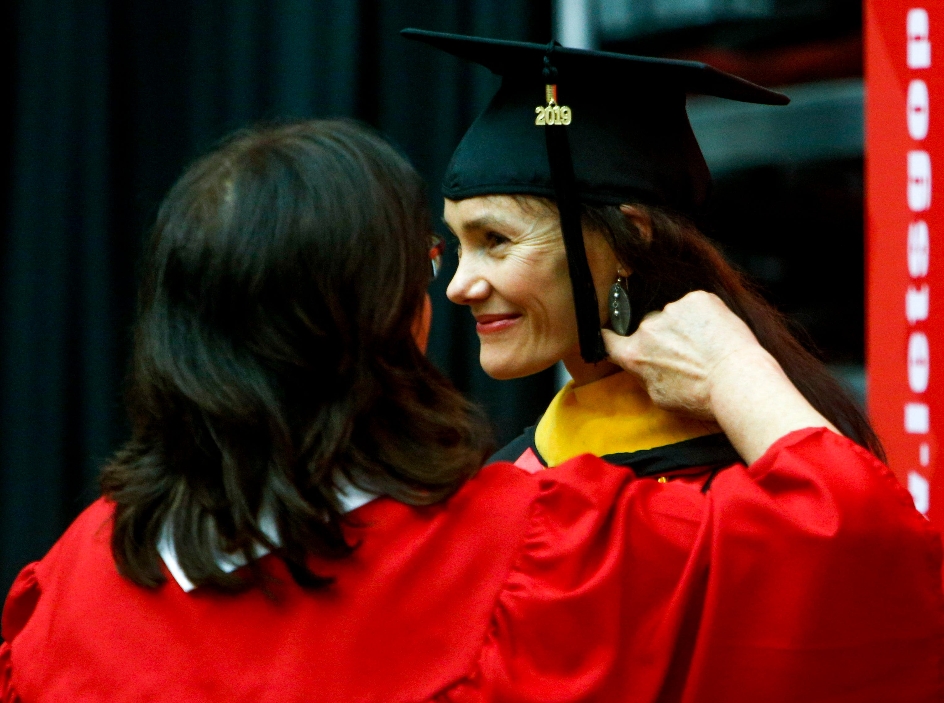 An administrator helps adjust the hair of a graduate student at the Austin Peay spring commencement ceremony 2019 for College of Business and College of STEM at Winfield Dunn Center in Clarksville, Tenn., on Friday, May 3, 2019.