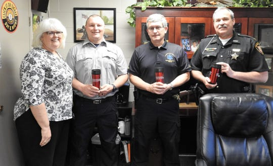 Beth Cormack of Coshocton Behavioral Health Choices gives tumblers to Nic Carey of the Coshocton Fire Department, Todd Shroyer of Coshocton County Emergency Medical Services and Sheriff Tim Rogers of the Coshocton County Sheriff's Office in recognition of agency contributions to the fight on drug and alcohol addiction.