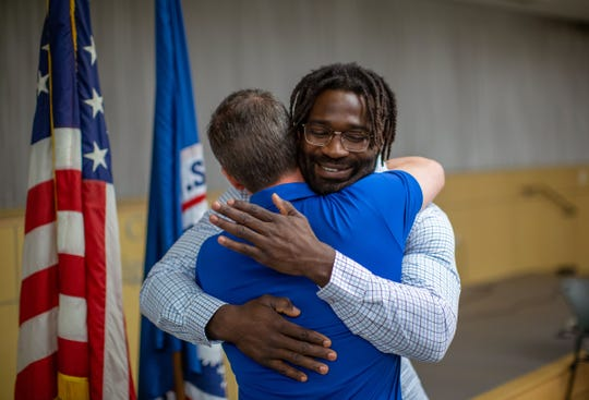 Detroit Lions linebacker Steve Longa hugs his agent Wesley Spencer after being sworn in as a U.S. citizen on Thursday, April 18, 2019 at U.S. Citizenship and Immigration Services in Detroit.