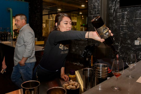 Mae Cagalingan of Warren, right, serves wine during Detroit Vineyards grand opening on Friday, May 3, 2019. The Detroit winemaker manufactures and sells wine, cider and mead at its facility on Gratiot Avenue.
