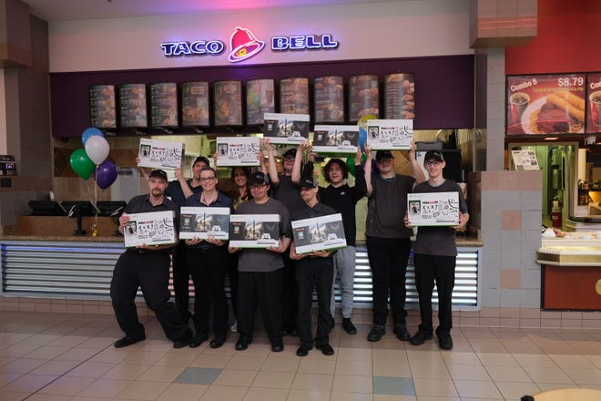 Employees of the Taco Bell in Midland Mall holding their new Xbox One S with Taco Bell's No. 1 RGM of the year/Golden Bell recipient, Jennifer Avery (second row, center)