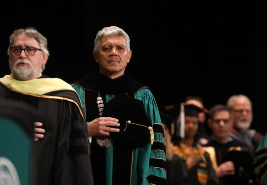 M. Roy Wilson, the president of Wayne State University stands at attention during the National Anthem during graduation ceremonies at the Fox Theatre in downtown Detroit on Friday, May 3, 2019.