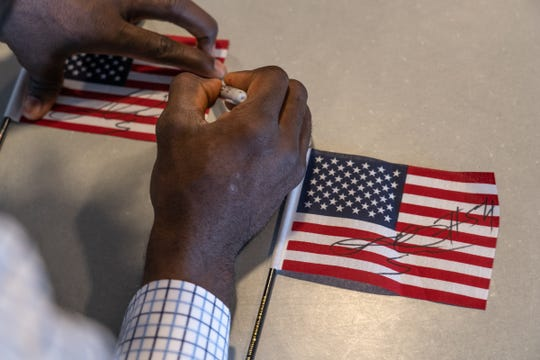 Lions linebacker Steve Longa autographs small flags for workers after becoming a U.S citizen on Thursday, April 18, 2019 at the U.S. Citizenship and Immigration Services in Detroit.