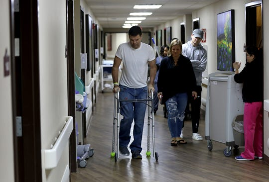 Greg Piscopink gets exercise at Maple Manor Rehab Center in Novi, Michigan to exercise down the hall on Friday, April 26, 2019 as wife Jennifer Piscopink and son Gregory watch him.