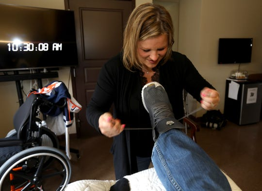 Jennifer Piscopink ties the shoes of husband Greg Piscopink after putting on his foot and ankle brace. Piscopink has been in the Maple Manor Rehab Center in Novi, Michigan since October 1st.