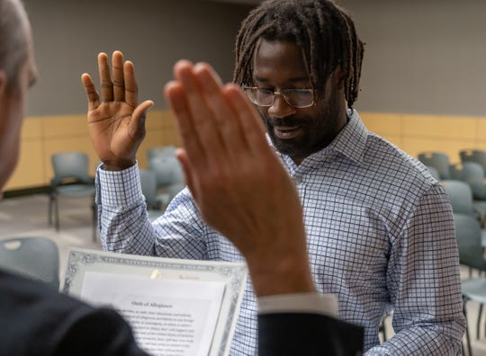 Lions linebacker Steve Longa is sworn in as a U.S citizen by U.S. Citizenship and Immigration Services district director Mick Dedvukaj after passing his test for citizenship on Thursday, April 18, 2019 at the U.S. Citizenship and Immigration Services in Detroit.