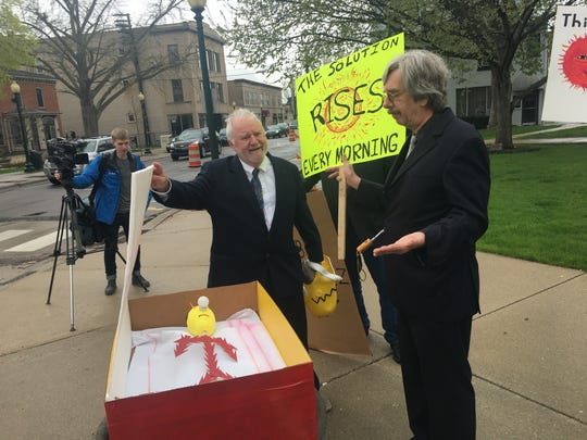 """Anti-nuclear activists Mark Farris (left) and Keith Gunter took part in a """"funeral"""" for nuclear power on April 30, 2019 in downtown Monroe. They stand over the """"coffin"""" of the old power industry mascot Reddy Kilowatt."""