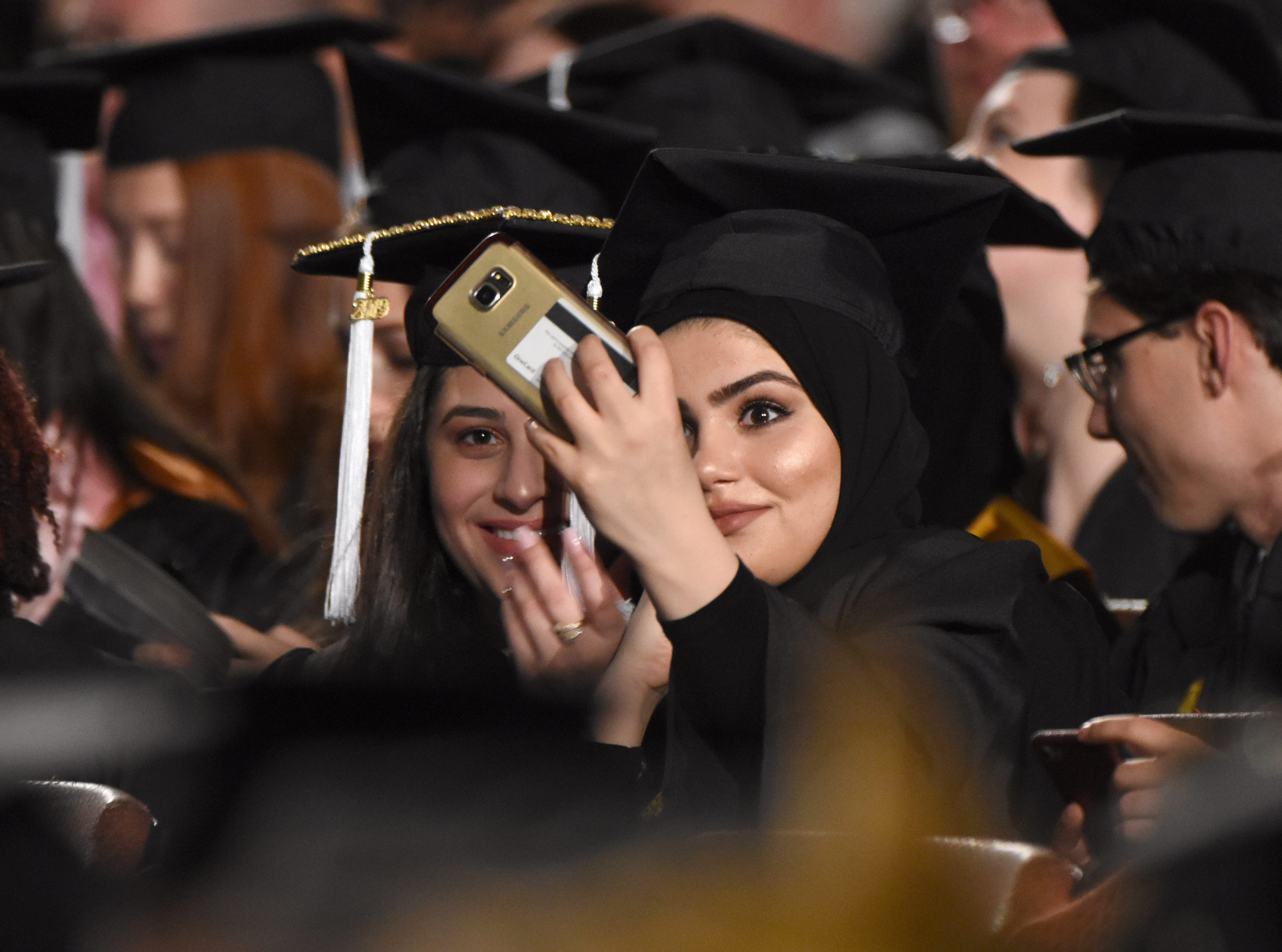 Wayne State University graduates take photographs during commencement exercises at the Fox Theater on Friday, May 3, 2019.