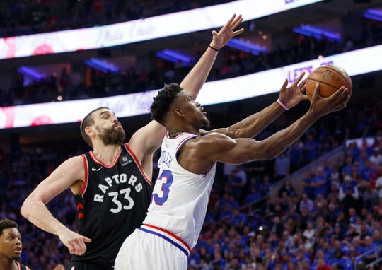 Philadelphia 76ers' Jimmy Butler, right, goes up for the shot against Toronto Raptors' Marc Gasol, left, during the second half.
