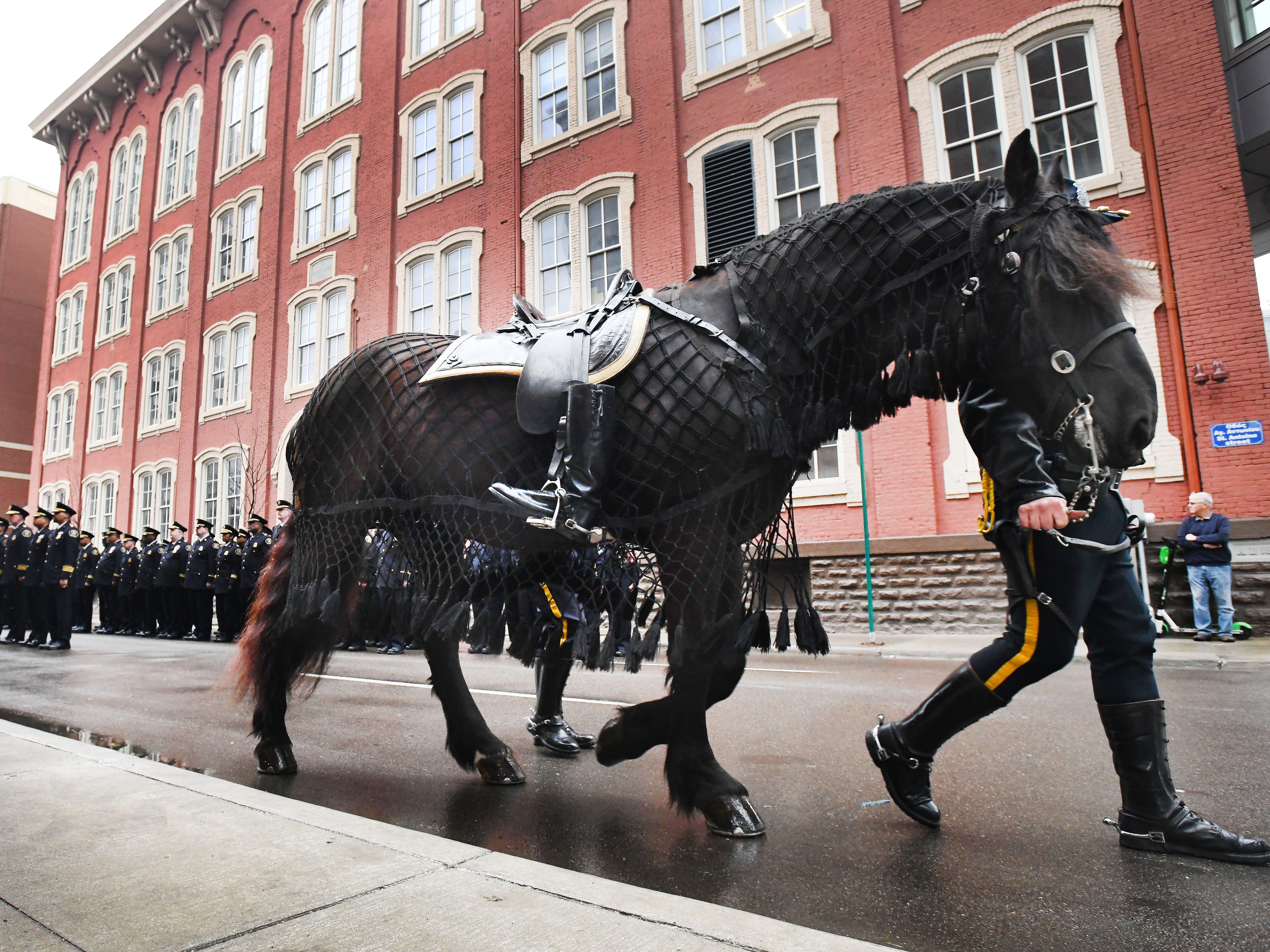A riderless horse, with boots reversed in the stirrups, passes by the officers before the 46th Annual Detroit Police Interfaith Memorial Service.