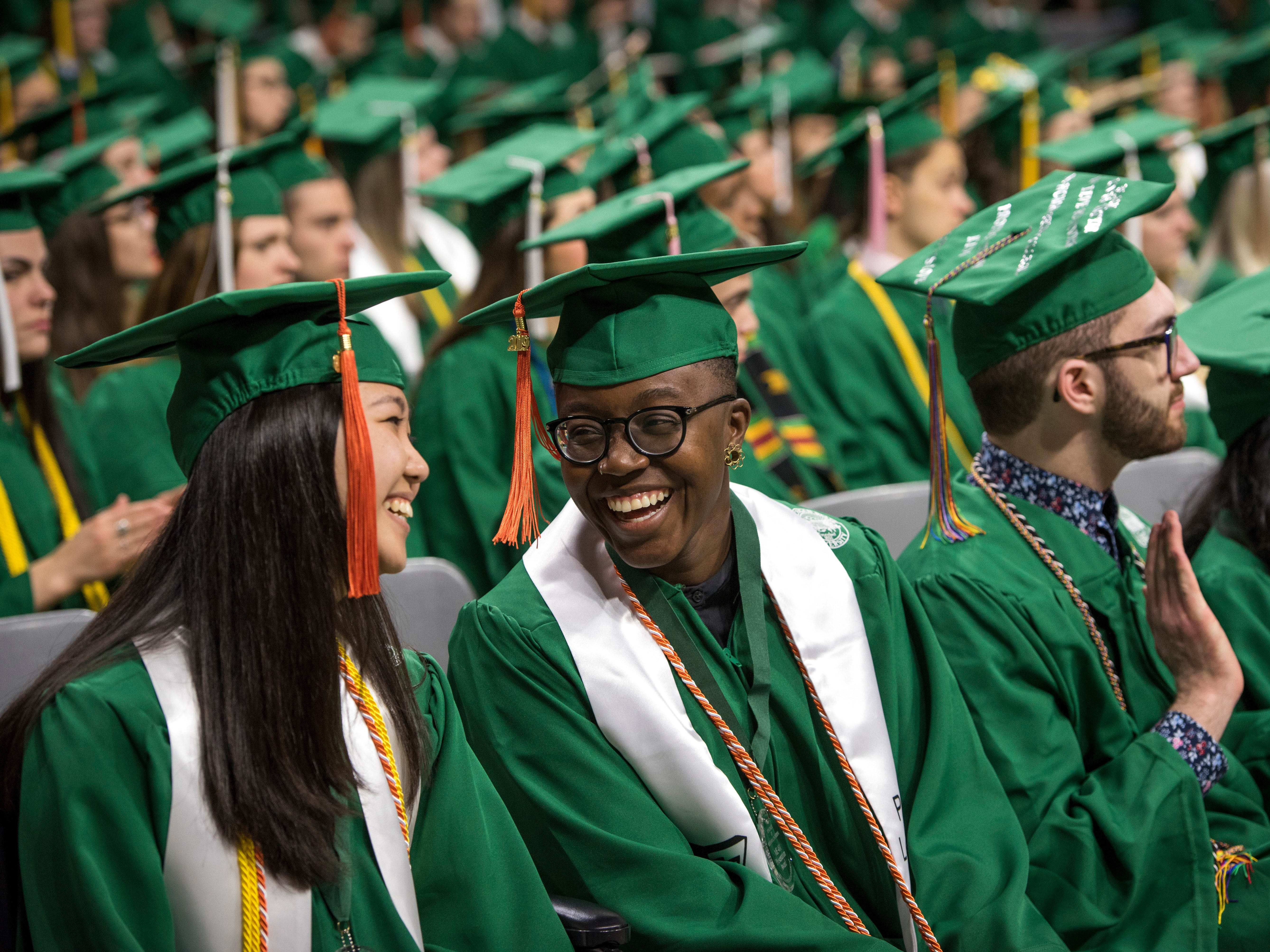 Mechanical engineering graduates Allison Nielsen, left, and Mimi Asante share a laugh during Michigan State University's Spring Commencement ceremony at Breslin Center in East Lansing on Friday, May 3, 2019.