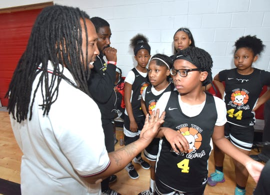 Top Ten Bad Girls head coach Antwone Jefferson, left, of Detroit, talks to his team during halftime, including, starting point-guard Colleena Bryant (wearing glasses) during a Detroit PAL (Police Athletic League) youth basketball tournament.