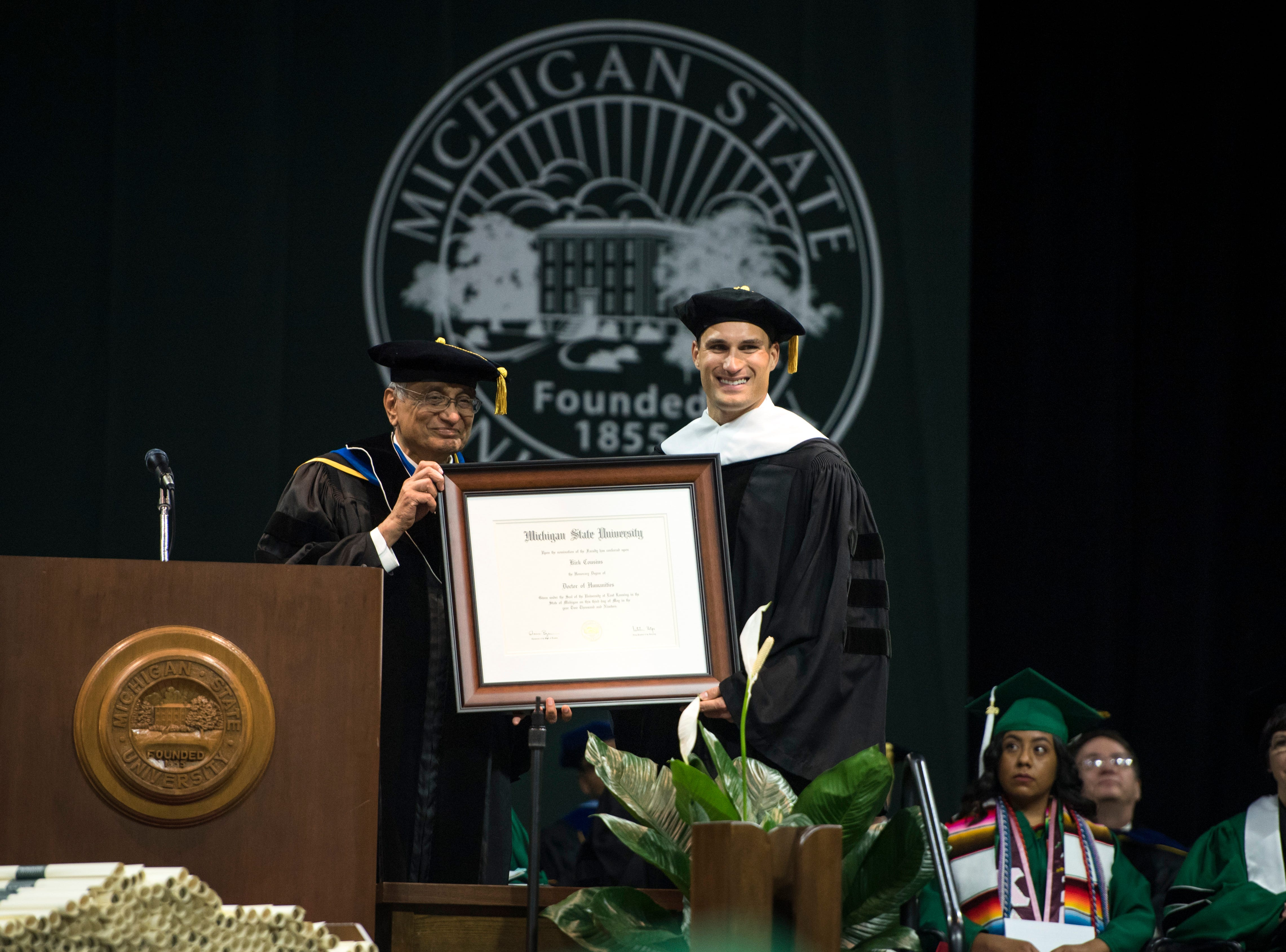 Michigan State University acting President Satish Udpa presents MSU alumnus and Minnesota Vikings Quarterback Kirk Cousins with an honorary degree.