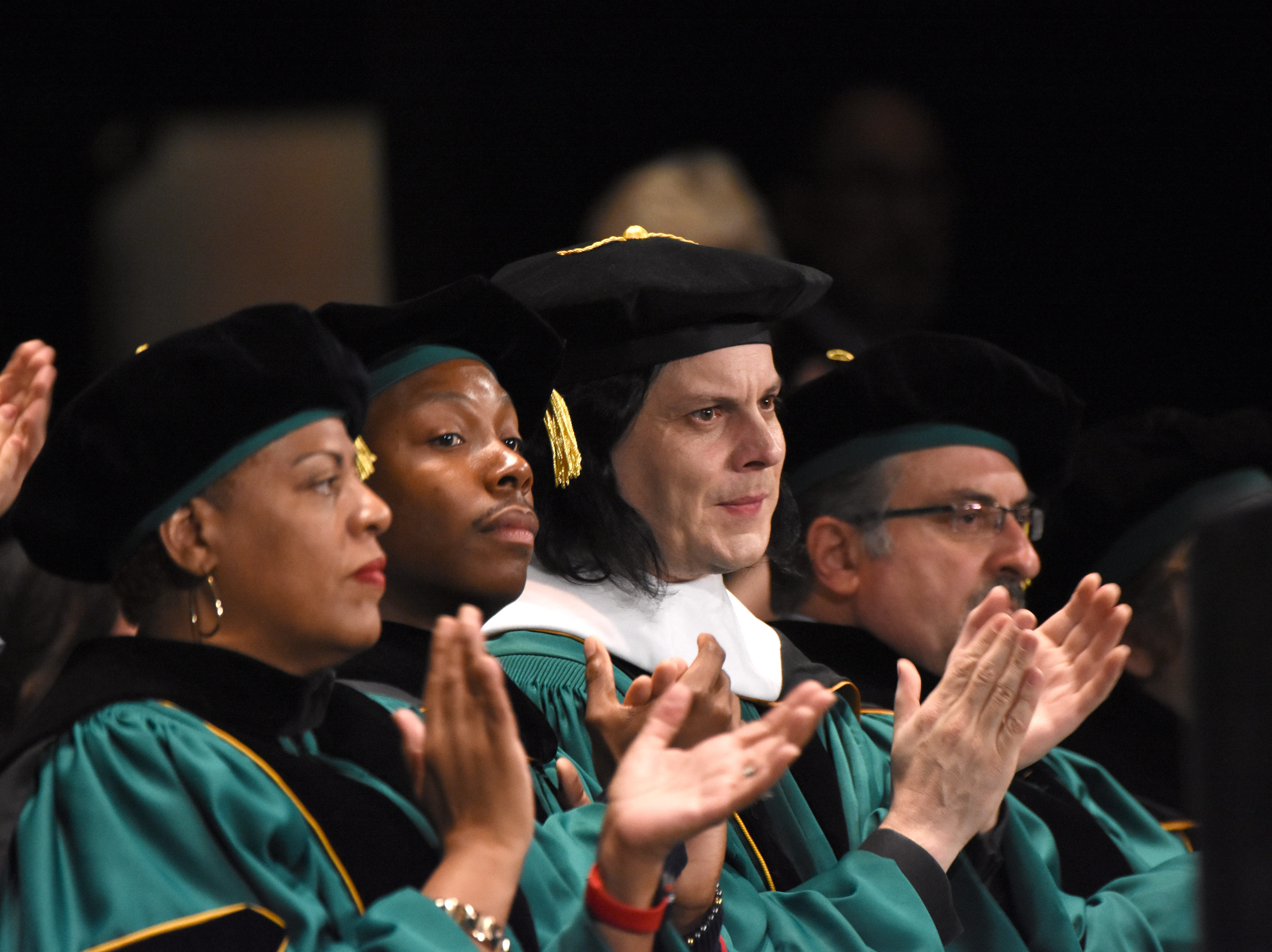 Musician Jack White claps moments after receiving an honorary degree during the Wayne State University commencement exercises at the Fox Theatre on Friday, May 3, 2019.