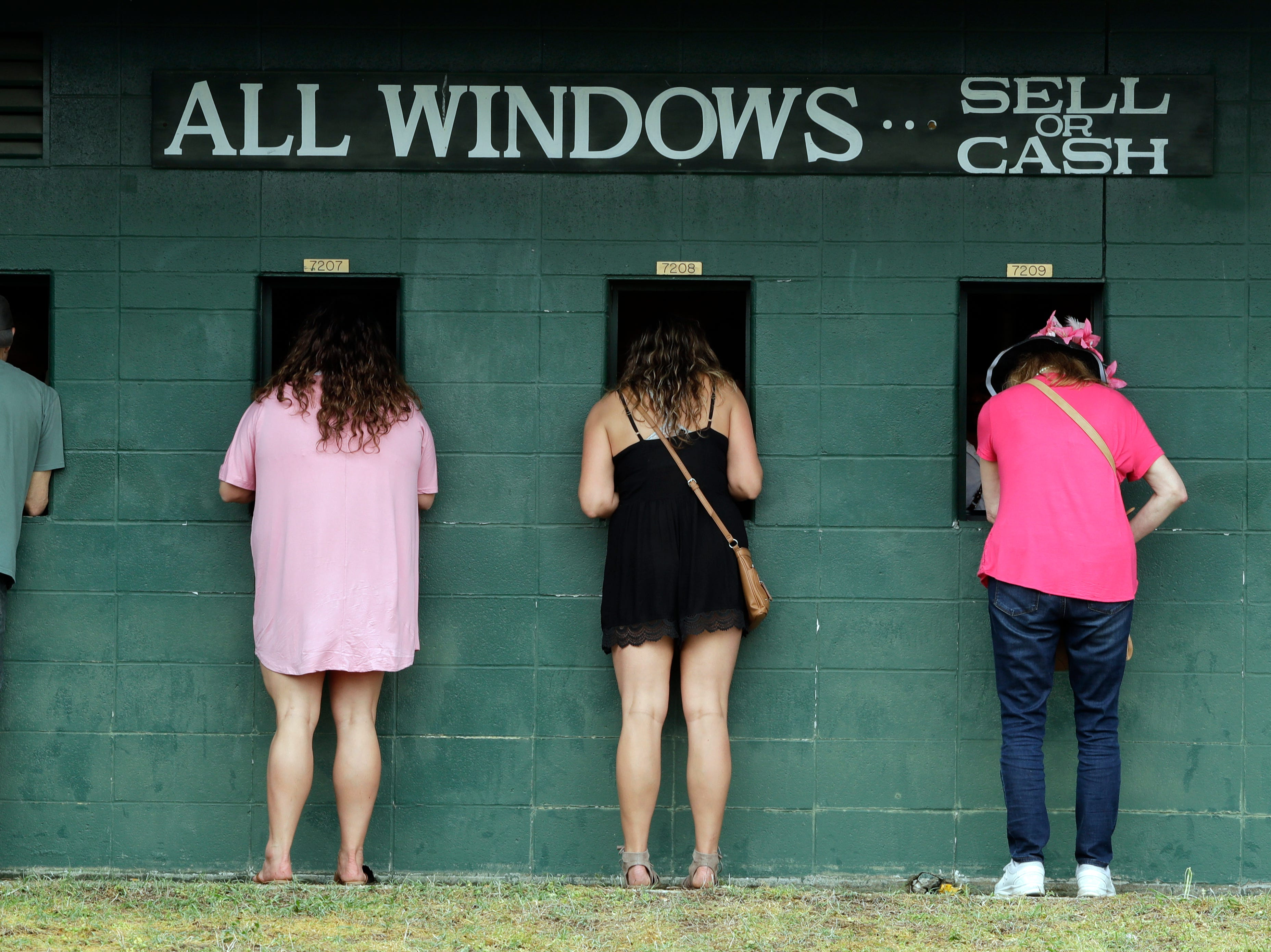 Fans place bets before the 145th running of the Kentucky Oaks horse race at Churchill Downs Friday, May 3, 2019, in Louisville, Ky.